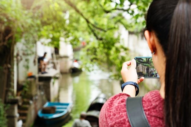 Junge frau, die spaß in der lokalen kanalstadt in china mit kamera auf dem smartphone macht bilder hat