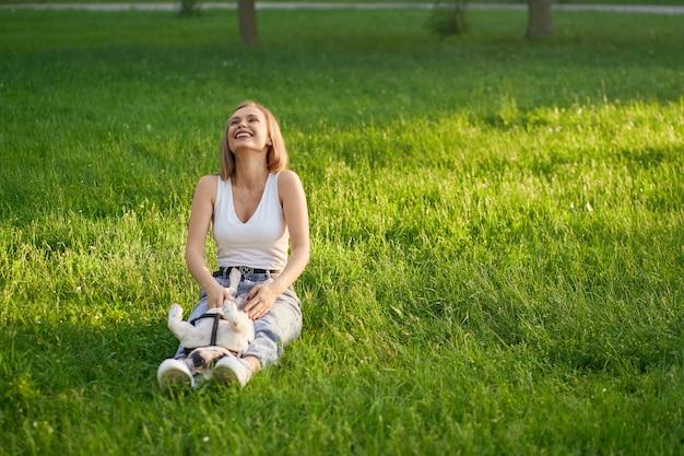 Junge frau, die spaß mit französischer bulldogge auf gras hat