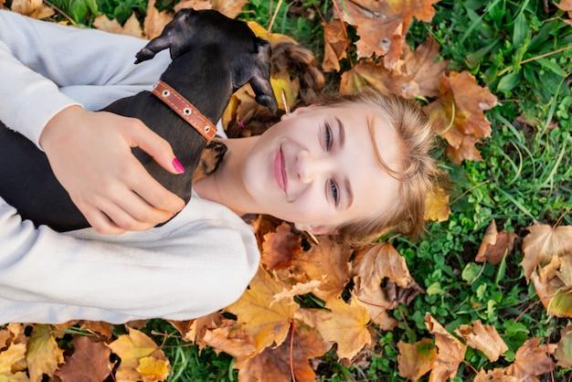 Junge frau, die spaß mit ihrem dachshundhund spielt auf dem gras hat
