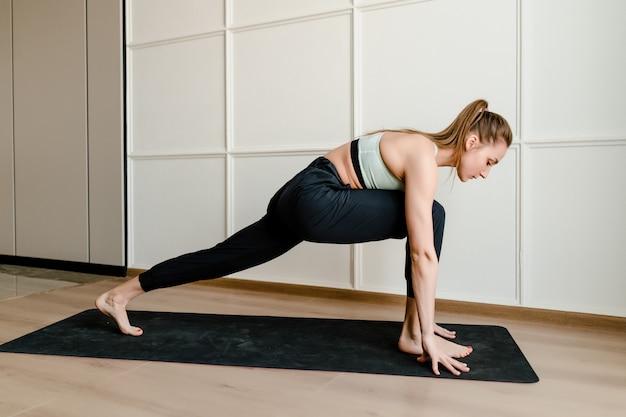 Junge frau, die sport auf yogamatte zu hause tut