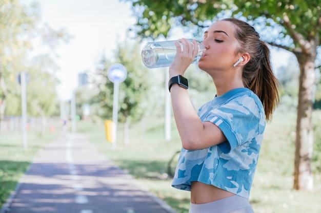 Junge frau, die sportkleidung trinkwasser trägt