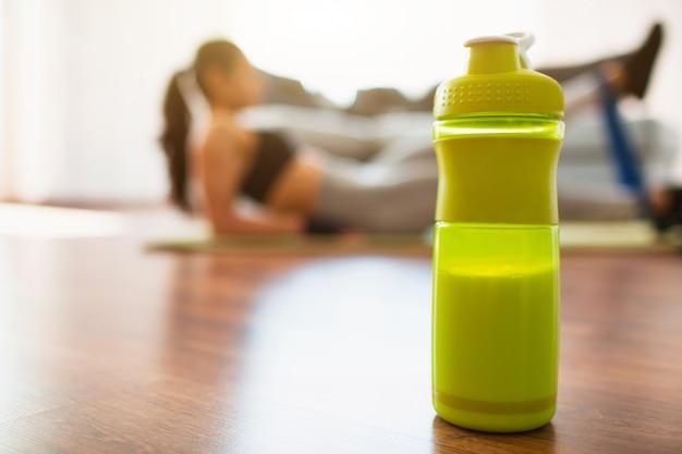 Junge frau, die sporttraining im raum tut. mädchen, das mit resistnace-band auf beinen ausübt. grüne proteinflasche steht vorne.
