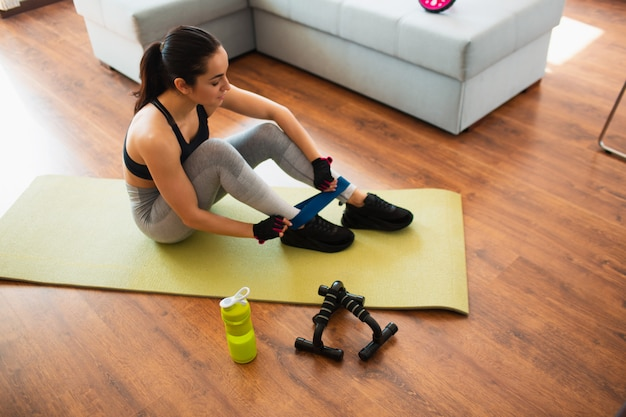 Junge frau, die sporttraining im raum tut. mädchen sitzen auf matte und setzen auf beinwiderstandsband. machen sie sich bereit für das training im zimmer.