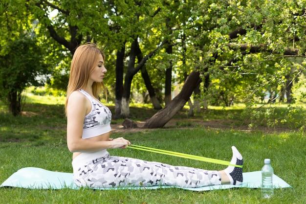 Junge frau, die sporttraining mit fitness-zahnfleisch im park tut