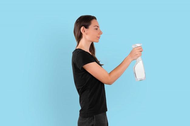 Junge frau, die sprühplastikflasche mit reinigungsflüssigkeit hält. frühjahrsputzkonzept. desinfizieren