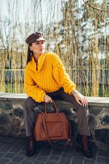 Junge frau, die stilvolle handtasche hält und gelben pullover im freien trägt. frühling weibliche kleidung und accessoires. mode. farbe von 2021