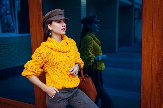 Junge frau, die stilvollen gelben pullover trägt und handtasche im freien hält. frühling weibliche kleidung und accessoires. straßenmode. farbe von 2021