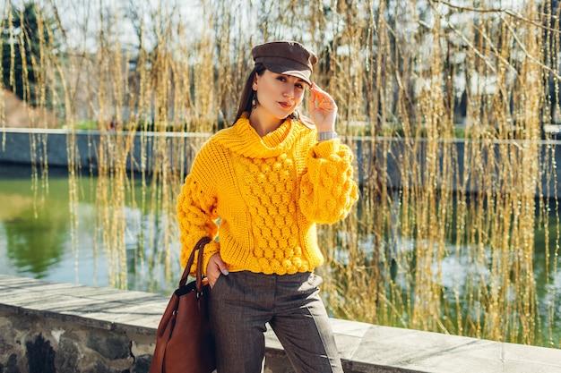 Junge frau, die stilvolles outfit trägt und handtasche im freien hält. frühling weibliche kleidung und accessoires. straßenmode. farbe von 2021