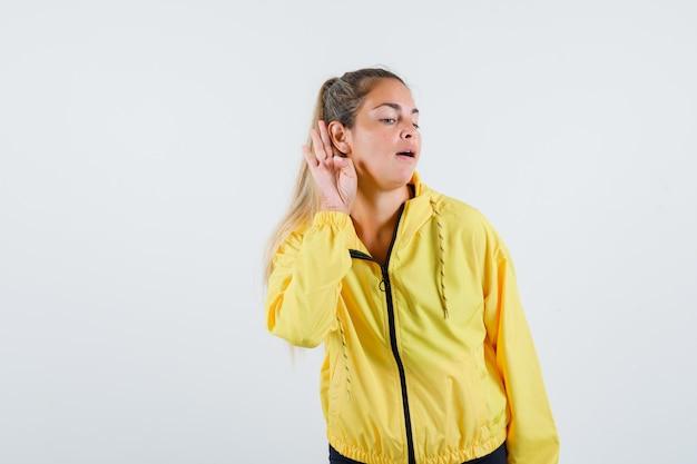 Junge frau, die stimmen im gelben regenmantel hört und vorsichtig schaut
