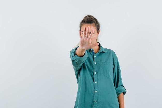 Junge frau, die stoppgeste im blauen hemd zeigt und ernst schaut