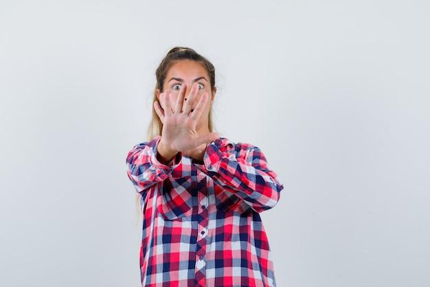 Junge frau, die stoppgeste im freizeithemd zeigt und ängstlich, vorderansicht schaut.