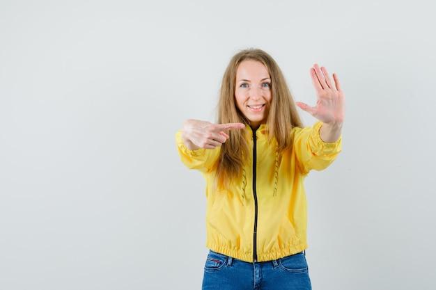 Junge frau, die stoppschild mit einer hand zeigt und in gelber bomberjacke und blauer jeans darauf zeigt und optimistisch, vorderansicht schaut.