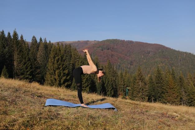 Junge frau, die streckübungen auf natur in den bergen tut. sportmädchen, das yoga-haltung in leggings praktiziert. schöne waldlandschaft