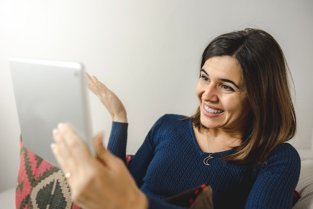 Junge frau, die tablet für einen videoanruf an freunde oder familie verwendet, glücklich und lächelnd während des gesprächs.