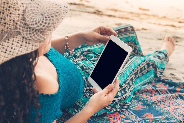Junge frau, die tablette auf strand verwendet