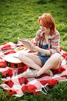 Junge frau, die tablette im freien am picknick und lächelnd verwendet