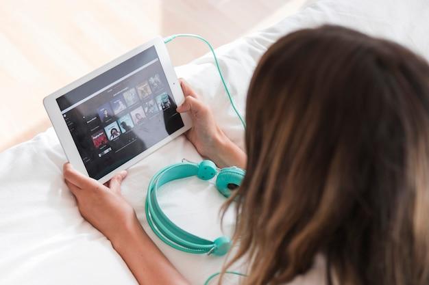 Junge frau, die tablette mit spotify app hält