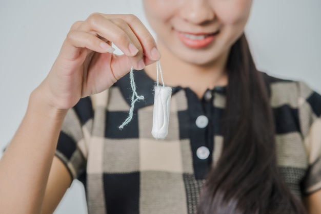 Junge frau, die tampon hält, der sich während des kritischen tages, der gynäkologischen gesundheitspflege, des menstruationszyklus krank fühlt.