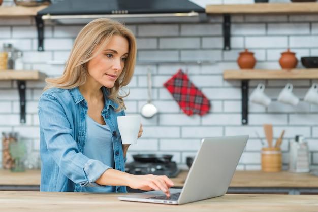 Junge frau, die tasse kaffee schreibt auf laptop in der küche hält