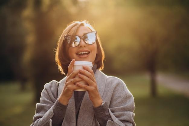 Junge frau, die tasse warmen kaffee im park hält