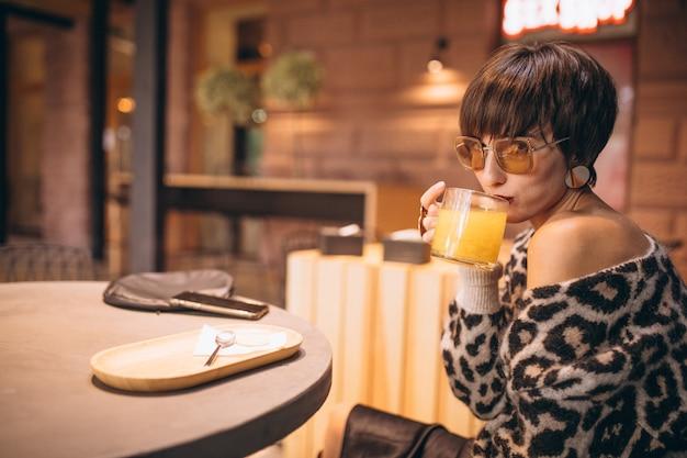 Junge frau, die tee in einem café trinkt