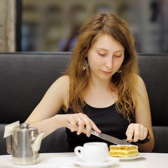 Junge frau, die tee und nachtisch in einem café trinkt