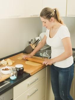 Junge frau, die teig mit holzstift auf küche rollt
