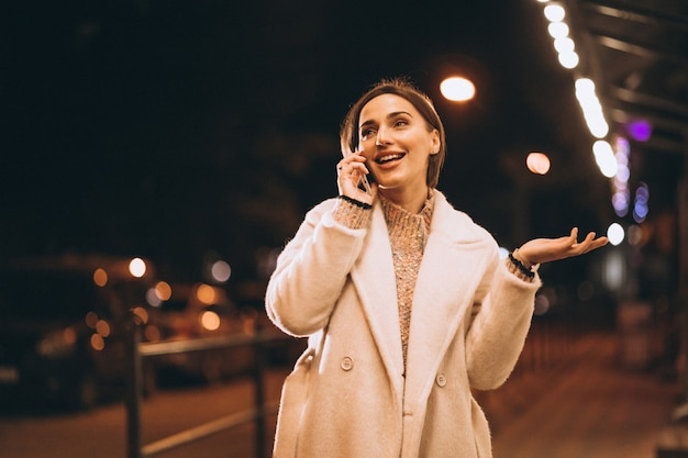 Junge frau, die telefon außerhalb der nachtstraße verwendet