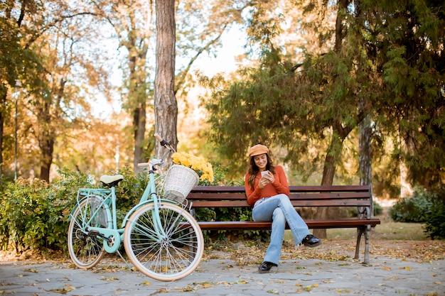 Junge frau, die telefon im herbstpark sitzt auf bank mit dem fahrrad verwendet