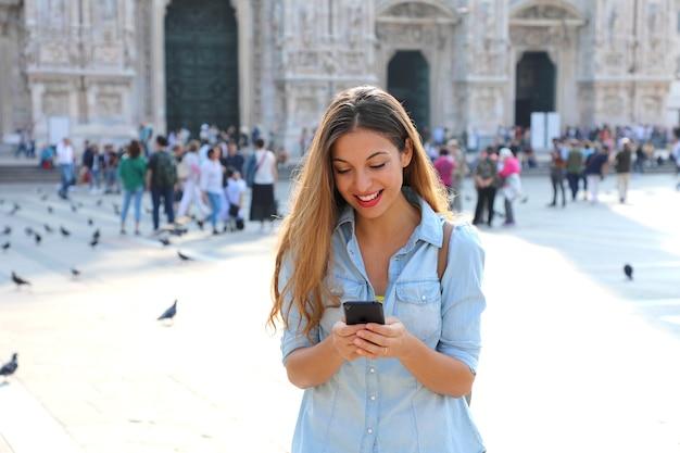 Junge frau, die telefon in mailand in italien benutzt