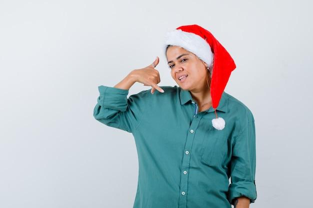 Junge frau, die telefongeste im hemd, in der weihnachtsmannmütze zeigt und selbstbewusst aussieht. vorderansicht.