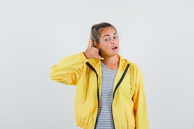 Junge frau, die telefongeste im t-shirt, in der jacke zeigt und selbstbewusst, vorderansicht schaut.