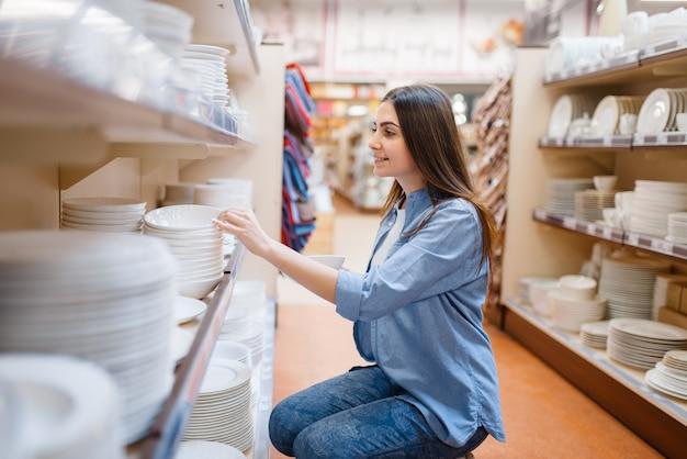 Junge frau, die teller im haushaltswarenladen wählt. weibliche person, die haushaltswaren im markt kauft, dame im küchengeschirrversorgungsgeschäft