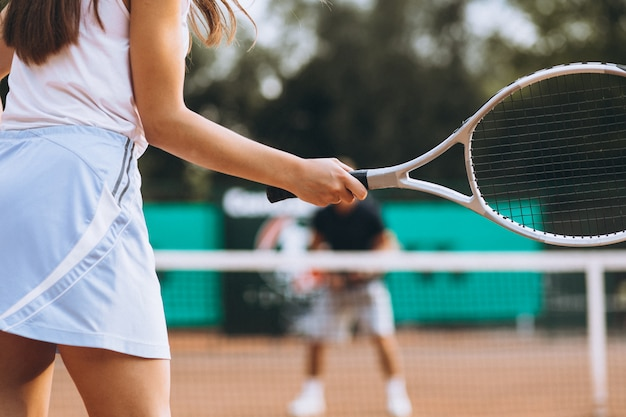 Junge frau, die tennis am gericht spielt
