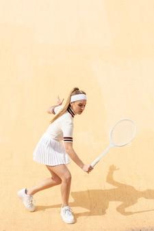Junge frau, die tennis auf feld spielt