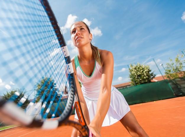 Junge frau, die tennis spielt