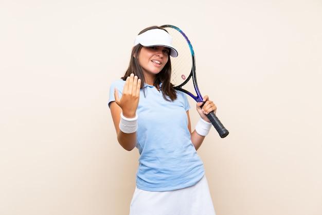 Junge frau, die tennis über der lokalisierten wand einlädt, mit der hand zu kommen spielt. schön, dass sie gekommen sind