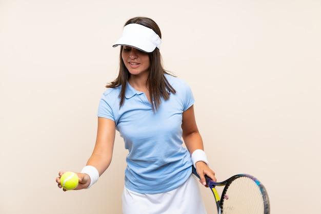 Junge frau, die tennis über lokalisierter wand spielt