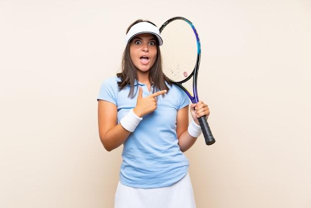 Junge frau, die tennis über lokalisierter wand überrascht spielt und seite zeigt