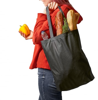 Junge frau, die textileinkaufstüte mit lebensmitteleinkauf hält. nachhaltiges lifestyle-konzept.