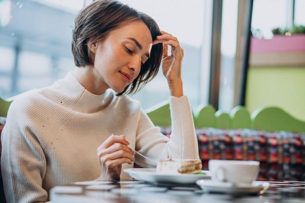 Junge frau, die tiramisu mit tee an einem café isst