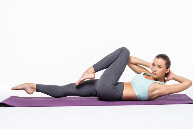 Junge frau, die trainiert und einen crunch tut, um ihre bauchmuskeln isoliert zu arbeiten