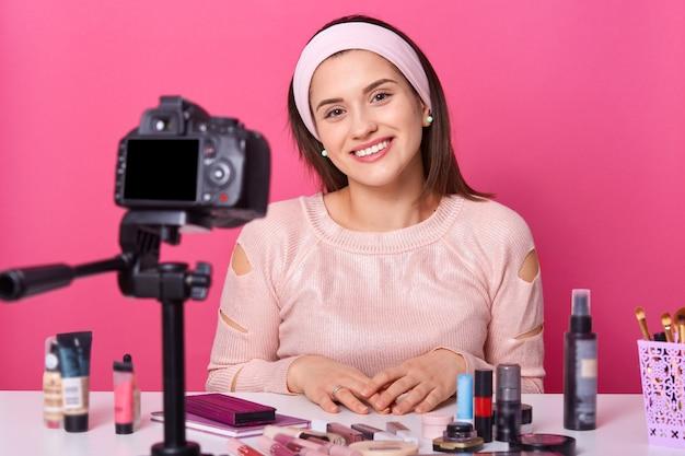 Junge frau, die über kamera auf stativ für ihren vlog über kosmetik aufzeichnet