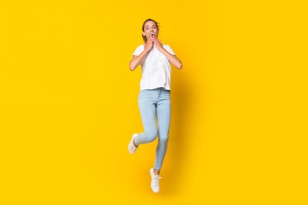 Junge frau, die über lokalisierte gelbe wand springt