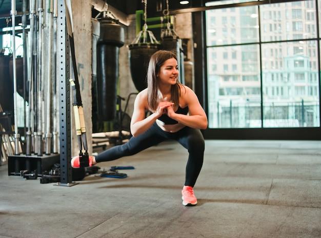 Junge frau, die übung für beine auf trx im fitnessstudio tut.
