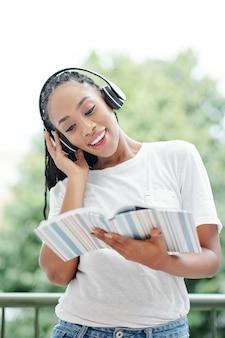 Junge frau, die übung im englischen lehrbuch macht, sie hört sprecher in den kopfhörern und wiederholt nach ihm
