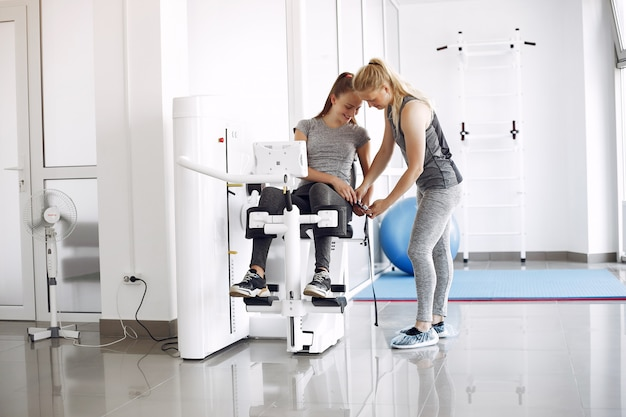 Junge frau, die übungen auf simulator mit therapeut im fitnessstudio tut
