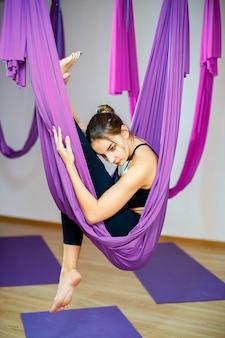 Junge frau, die übungen unter verwendung der hängematte ausdehnend tut. aerial yoga.