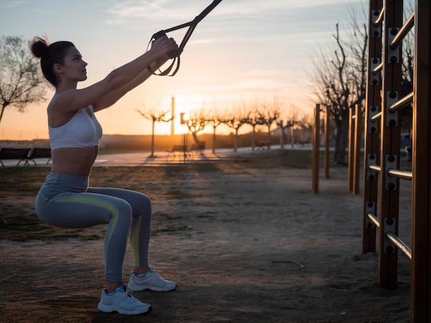Junge frau, die übungskniebeugen mit fitnessaufhängungsgurten im park trainiert. konzept sporttraining gesunden lebensstil. draussen