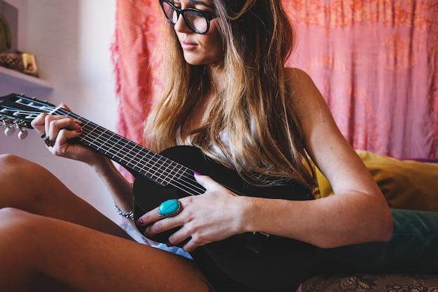 Junge frau, die ukulele auf bett spielt